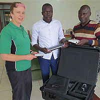 Asheri Stephen (extreme right), Entrepreneur for Rural Access (ERA) from Tanzania receiving the smart projector from Josephine Rodgers, Executive Director of Access Agriculture